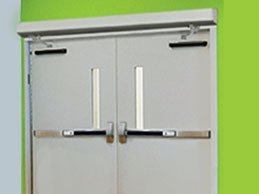 Swing Door Operator on a gray door in a school